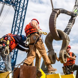 Workers adjust enormous clamps onto I Lift NY's rigging system